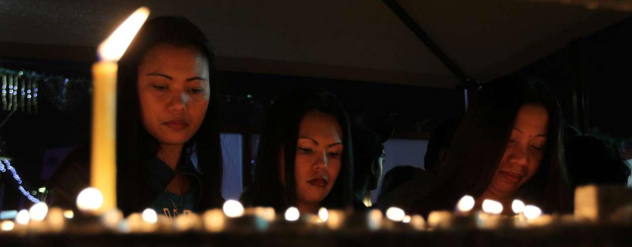 Cristianos encienden velas en la iglesia católica de Santa María durante la misa de Navidad.