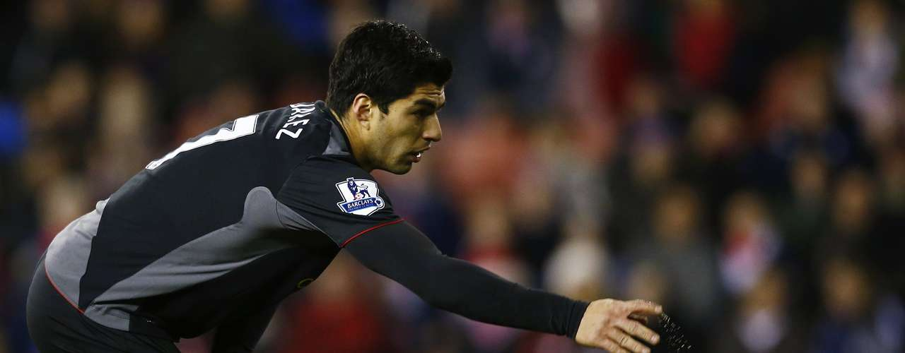 Liverpool's Luis Suarez throws a drink bottle from the pitch.