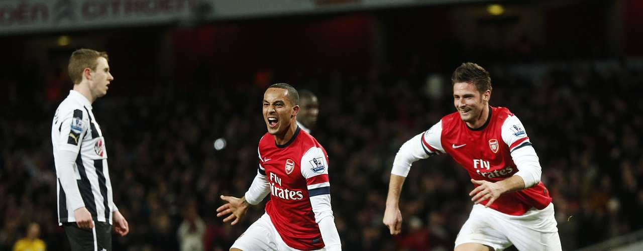 Walcott (C) celebrates as Olivier Giroud, who scored a brace, chases after him. REUTERS/Eddie Keogh