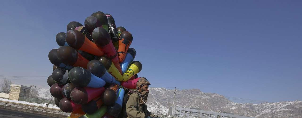 Un vendedor de globos traslada sus productos en una motocicleta por una calle de Kabul.
