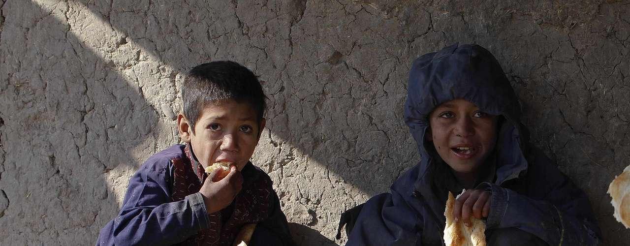 Dos niños refugiados comen en el suelo, sentados en una carretera.