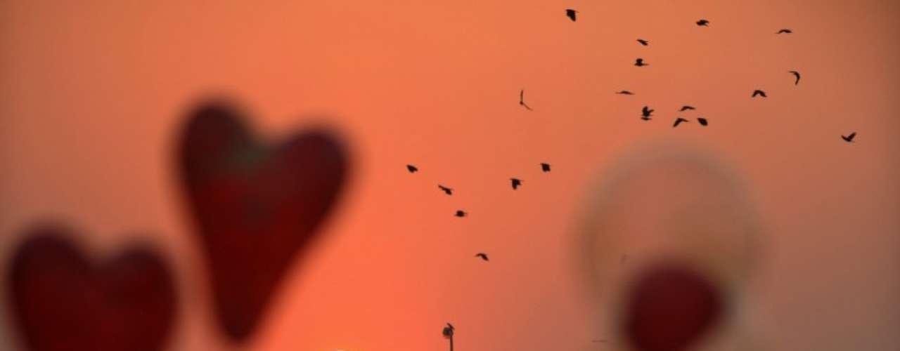 Globos en forma de corazón vuelan frente a la puesta de sol en la India acompañando a las aves que vuelan en el cielo antes de la llegada del Año Nuevo.