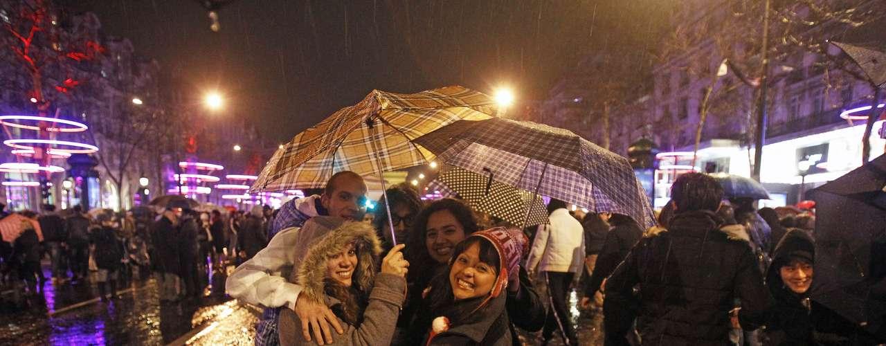 Pese a una lluvia ligera, franceses no bajaron el ánimo en la celebración por la llegada del año nuevo.