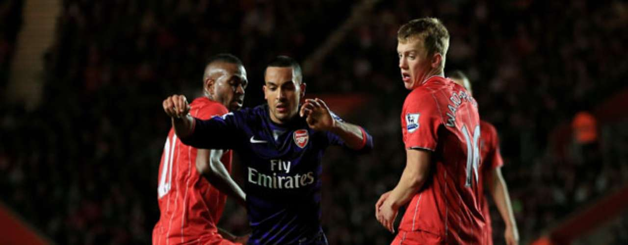 Theo Walcott is surrounded by Southampton players.