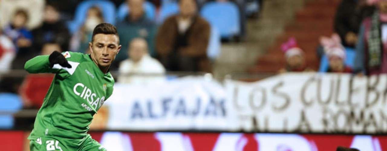 Betis' forward Ruben Castro (L) vies with Zaragoza's goalkeeper Roberto Jimenez.
