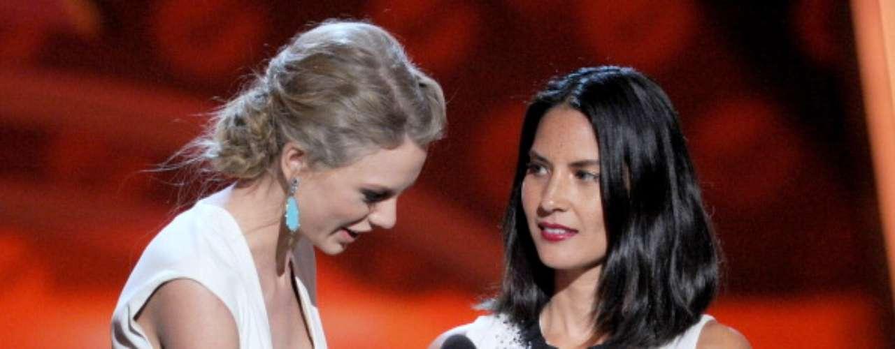 Taylor Swift trata de arrebatarle su estatuilla a la Cantante Favorita de Contry a quien se la otorgó, Olivia Munn (der.), quien no podía creer que tan rápido la bella cantante ya tuviera premios... el primero de muchos de la noche, seguramente.