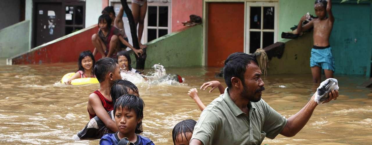 Un padre arrastra a su hijo a través de la riada.