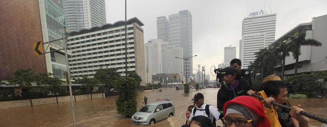 Mujeres indonesias son evacuadas en camiones de bomberos.