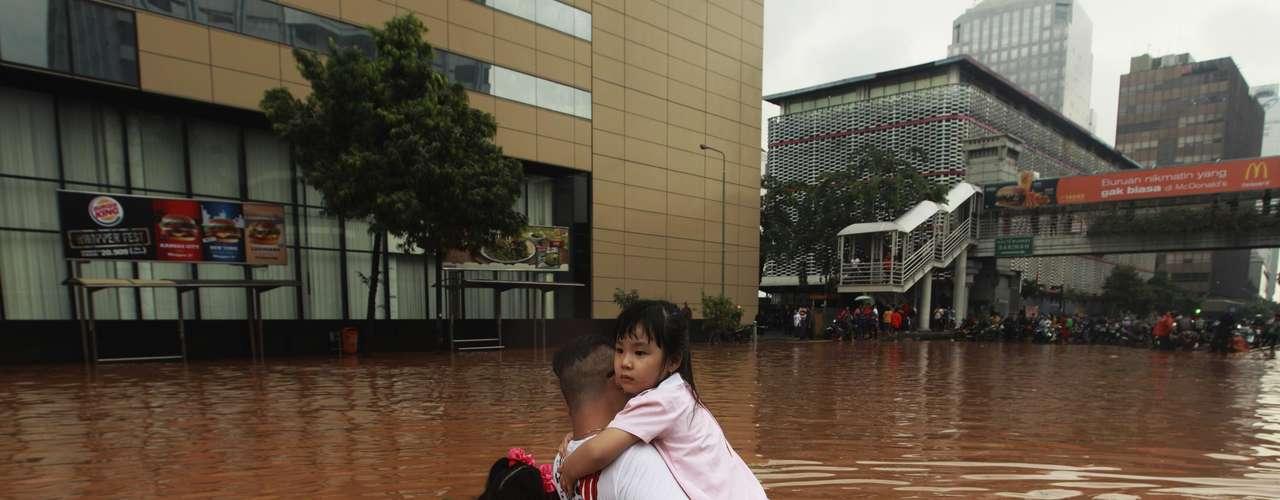 Un padre sujeta a sus hijos para poder cruzar una riada.