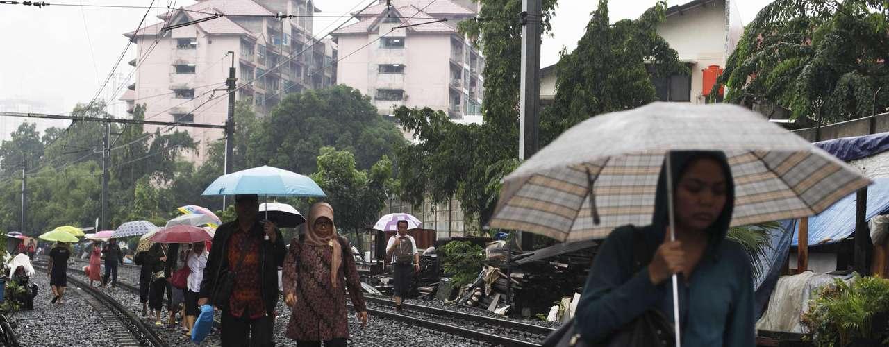 Trabajadores indonesios caminan por las vías del tren, ya que estos no pueden circular por las inundaciones.