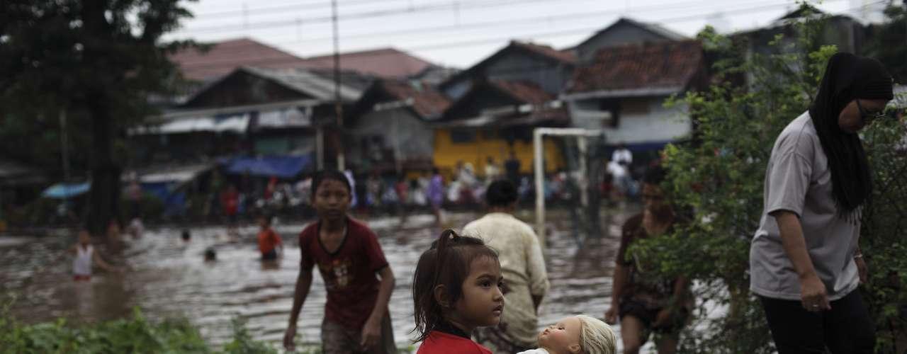 Una niña sujeta una muñeca sentada al lado de los caminos inundados.