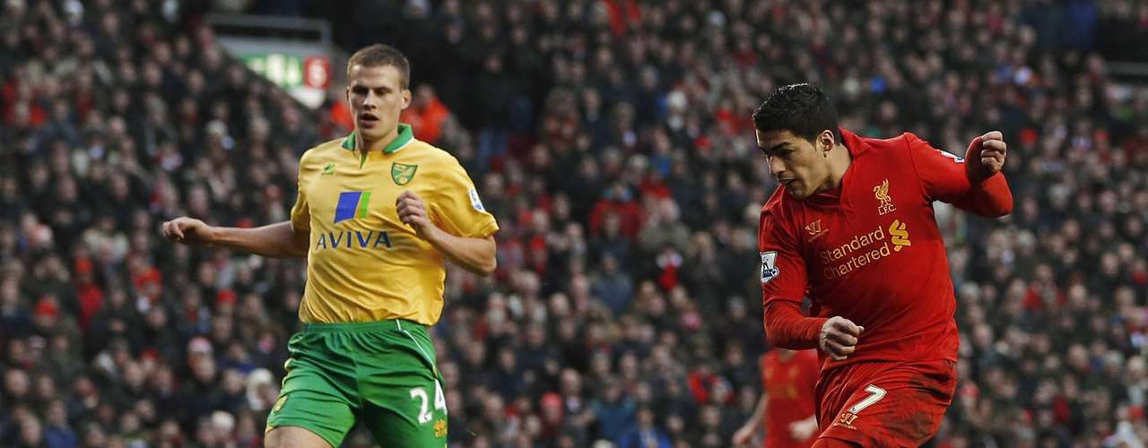 Liverpool's Luis Suarez (R) shoots past Norwich City's Ryan Bennett to score his sides second goal during their English Premier League soccer match at Anfield in Liverpool, northern England January 19, 2013. REUTERS/Phil Noble