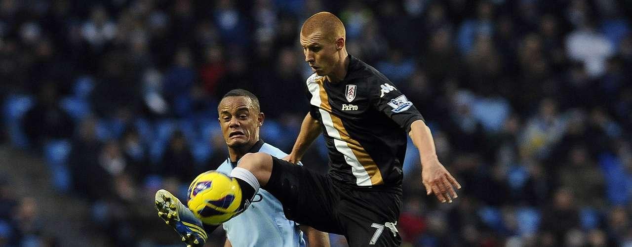 Manchester City's Vincent Kompany (L) challenges Fulham's Steven Sidwell. REUTERS/Nigel Roddis