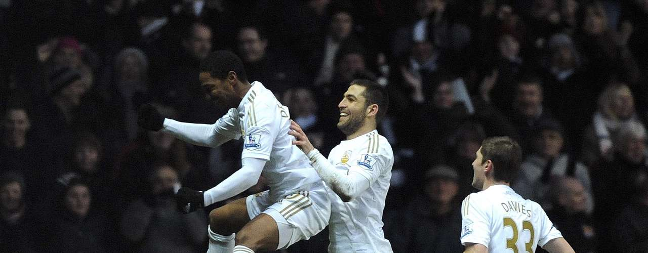 Swansea City's Jonathan De Guzman (L) celebrates with teammates after scoring from a free kick.