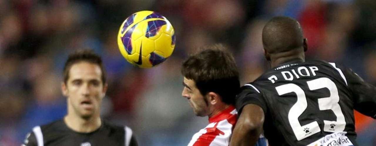 Adrián López (c), disputa un balón con el centrocampista senegalés del Levante, Papa Diop (d), durante el partido de la vigésima jornada de la liga disputado esta tarde en el estadio Vicente Calderón