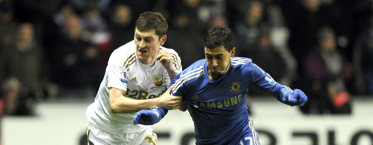 Swansea City's Ben Davies (L) challenges Chelsea's Eden Hazard during their English League Cup semi-final second leg soccer match at the Liberty Stadium in Swansea January 23, 2013.