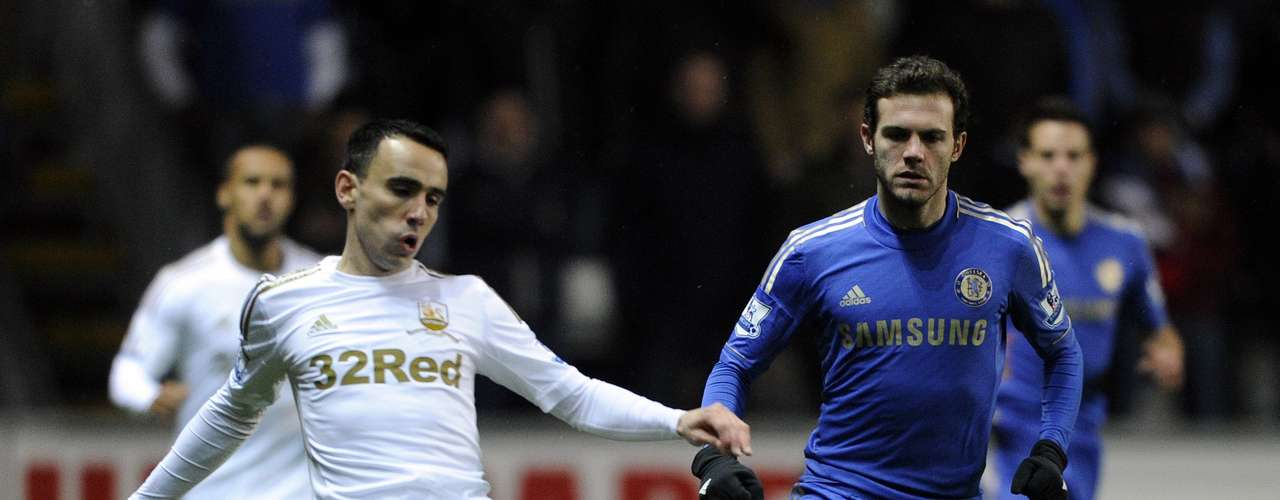 Swansea City's Leon Britton (L) passes the ball under pressure from Chelsea's Juan Mata during their English League Cup semi-final second leg soccer match at the Liberty Stadium in Swansea January 23, 2013.