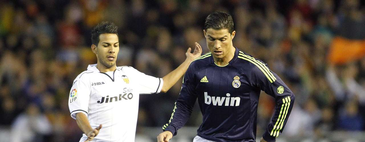Real Madrid's Cristiano Ronaldo (R) and Valencia's Joanathan Viera fight for the ball. REUTERS/Heino Kalis
