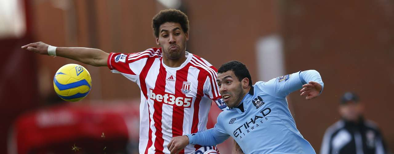 Stoke City's Ryan Shotton challenges Manchester City's Carlos Tevez (R) during their FA Cup fourth round soccer match.