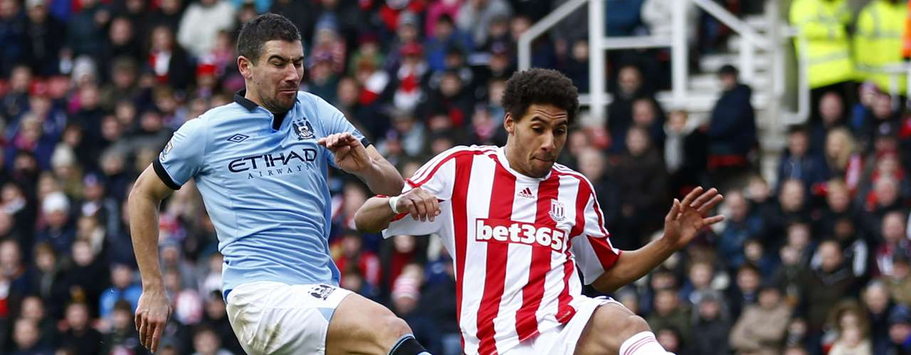 Stoke City's Ryan Shotton (R) challenges Manchester City's Aleksandar Kolarov.