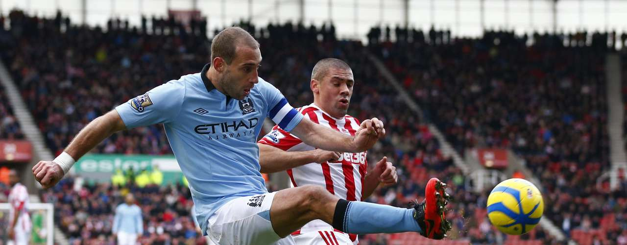 Stoke City's Jonathan Walters (R) challenges Manchester City's Pablo Zabaleta.