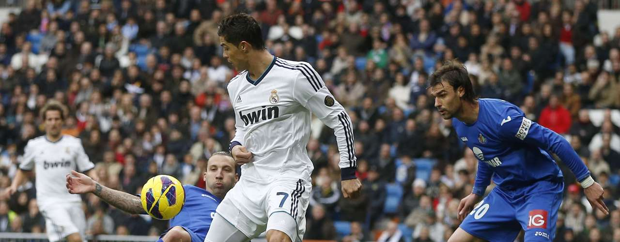Cristiano Ronaldo (C) fights for the ball with Getafe's Alexis Ruano (L) and Juan Valera.