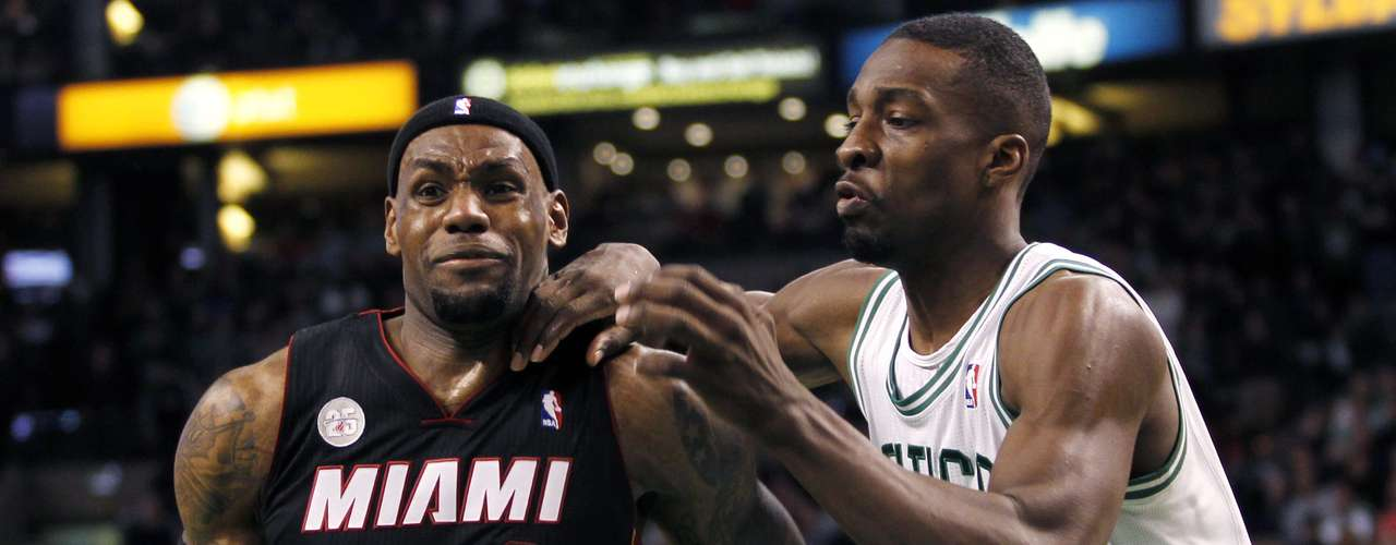 Miami Heat's LeBron James (L) drives past Boston Celtics' Jeff Green in overtime of their NBA basketball game at TD Garden in Boston, Massachusetts January 27, 2013.