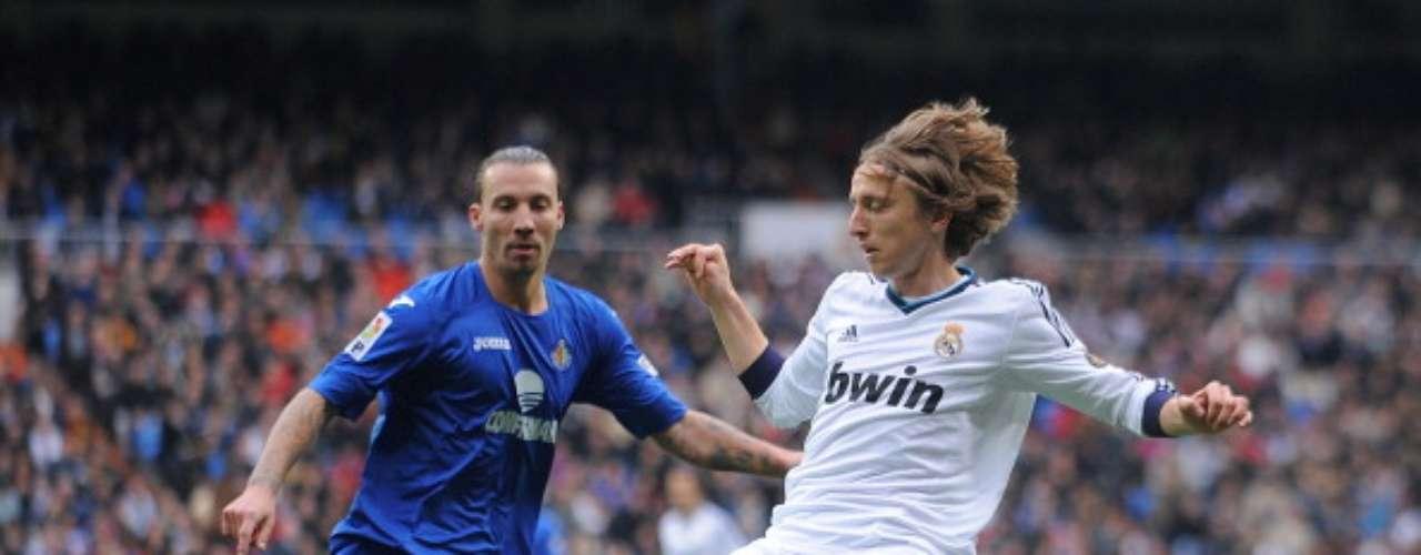 El croata Luka Modric trata de proteger el balón ante el acoso de Alexis Ruano.