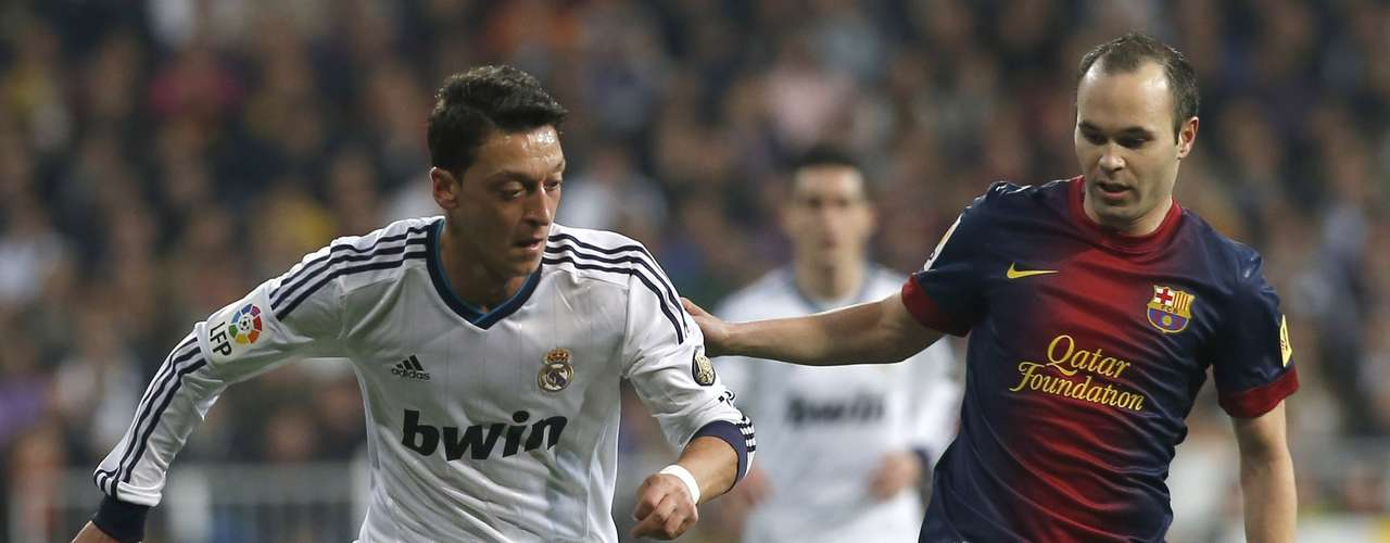 Mesut Ozil (L) fights for the ball with Andres Iniesta.