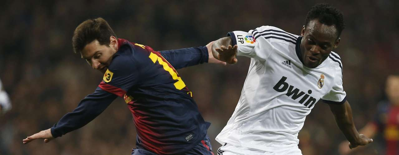 Lionel Messi (L) fights for the ball with Michael Essien.