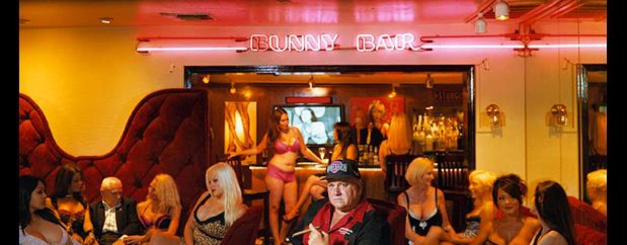 A client at the Bunny Bar enjoys a cigar surrounded by 11 sex workers.