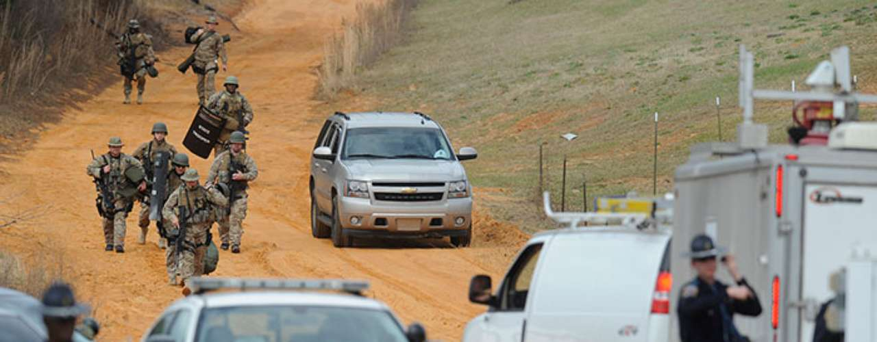 Some 50 federal, state and local vehicles surrounding the entrance to a dirt road near a federal road. The route ends in rustic dwellings including Dykes' property, which is on a hill not far behind a church high on the federal highway
