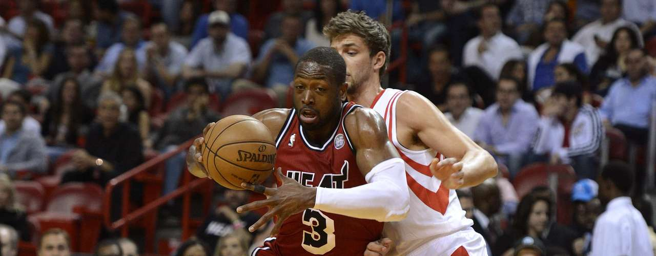 Miami Heat's Dwyane Wade (L) is defended by Houston Rockets' Chandler Parsons (R) during the first half of their NBA basketball game in Miami, Florida, February 6, 2013.