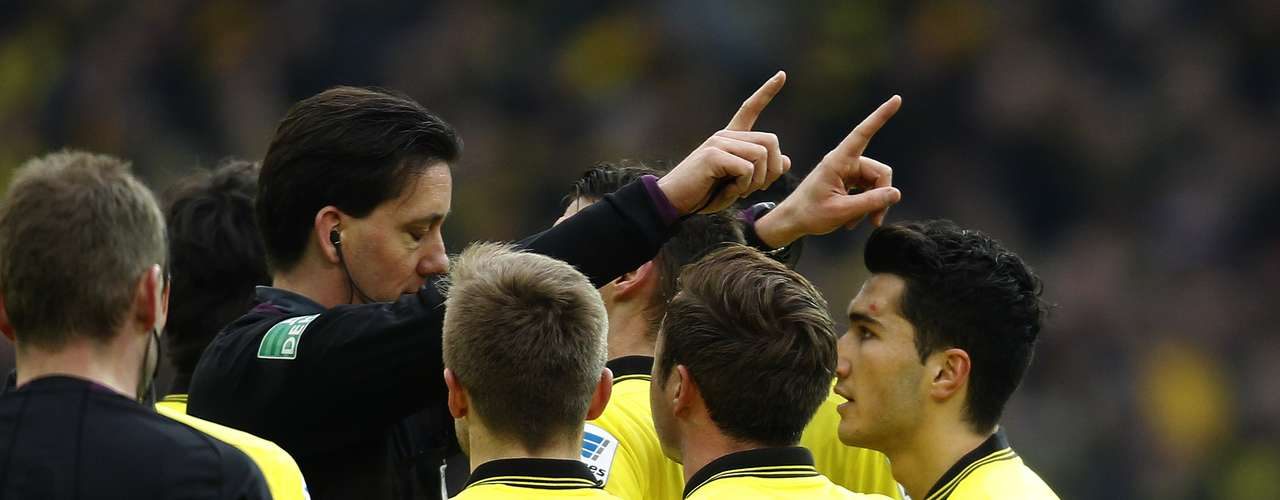 Referee Manuel Graefe (L) gestures to Borussia Dortmund's players during the German first division Bundesliga soccer match against Hamburger SV.
