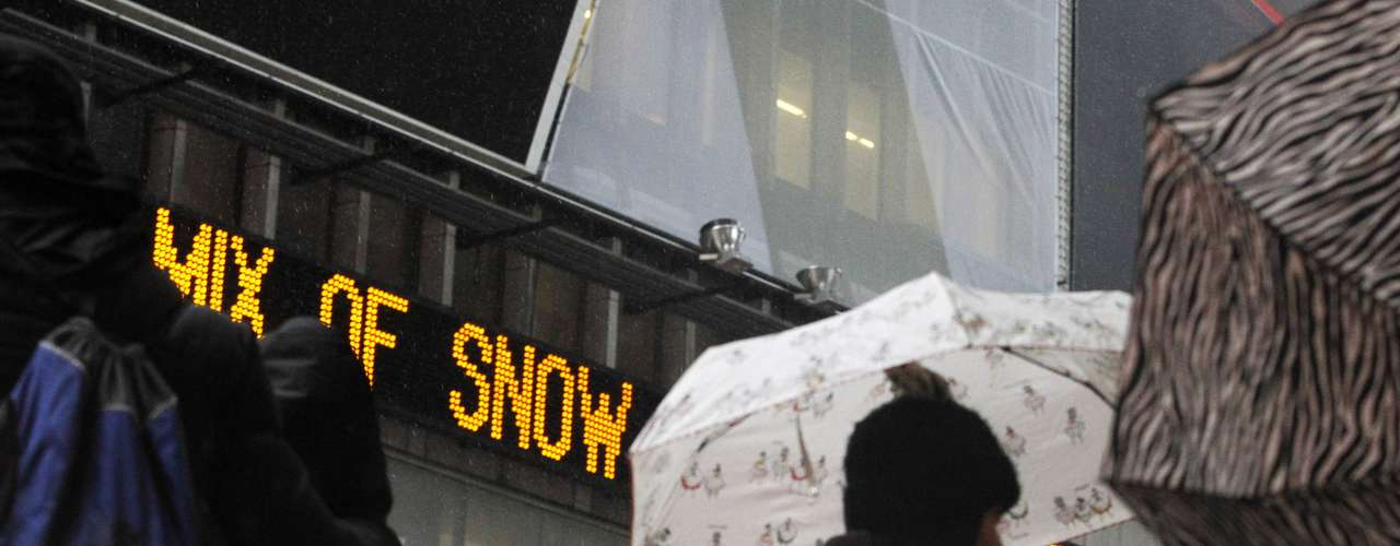 A weather report is displayed on a news scroll as people walk through Times Square in New York, February 8, 2013. The Northeast U.S. is bracing for a large winter storm that has caused flight cancellations. REUTERS/Brendan McDermid (UNITED STATES - Tags: ENVIRONMENT)