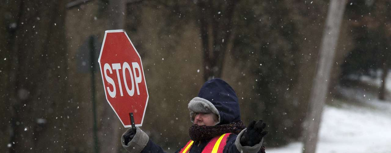 A crossing guard helps students at an intersection after schools closed early ahead of bad weather in Pelham, New York February 8, 2013. A blizzard blew into the northeastern United States on Friday, bringing whiteout conditions to some parts of New England and threatening to drop record amounts of snow around Boston. From New York to Maine, the storm began gently, dropping a light dusting of snow, but officials urged residents to stay home, rather than risk getting stuck in deep drifts when the storm kicks up later Friday afternoon. REUTERS/Adrees Latif  (UNITED STATES - Tags: ENVIRONMENT DISASTER EDUCATION)