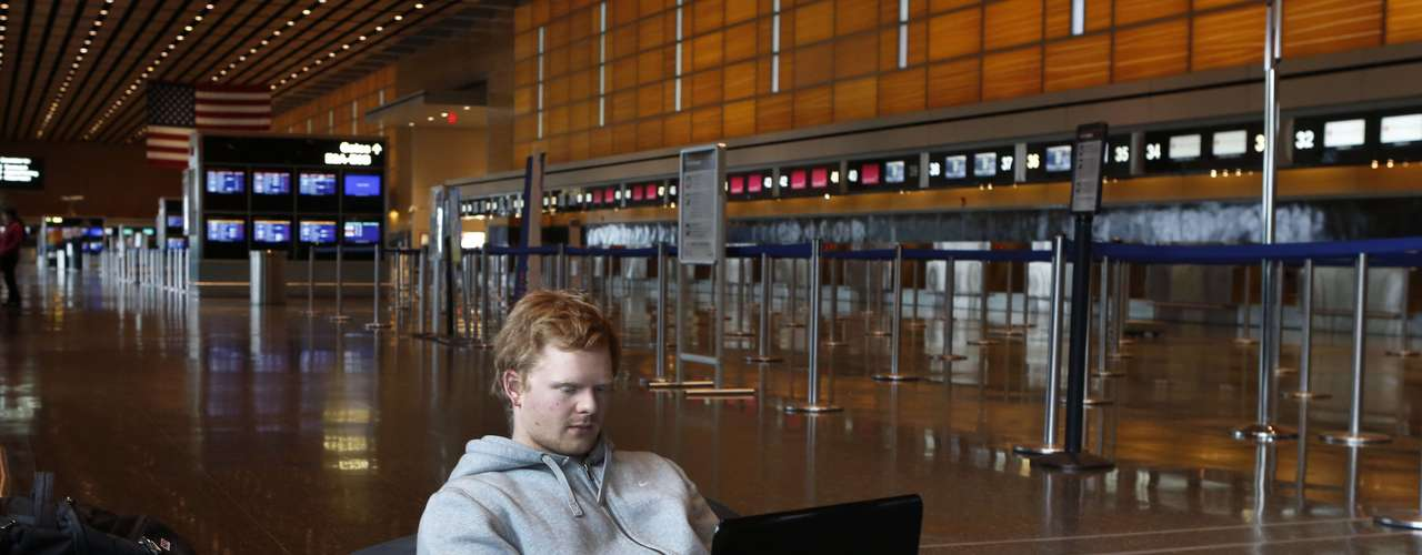 Rasmus Thomsen of Denmark works on his computer as he waits at Boston Logan International Airport after flights were cancelled or delayed due to a massive winter storm, in Boston, Massachusetts February 8, 2013. Blizzard warnings were in effect from New Jersey through southern Maine, with Boston expected to bear the brunt of the massive storm that could set records.   REUTERS/Bizuayehu Tesfaye   (UNITED STATES - Tags: ENVIRONMENT)