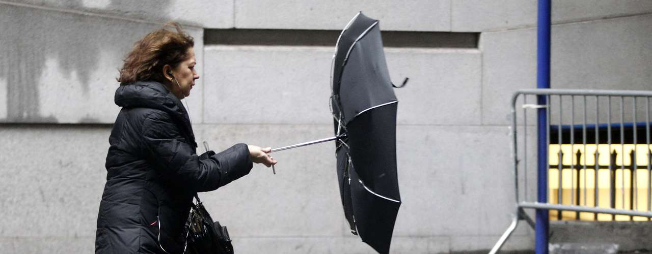 A woman struggles with an umbrella in New York's financial district, February 8, 2013. The Northeast U.S. is bracing for a large winter storm that has caused flight cancellations. REUTERS/Brendan McDermid (UNITED STATES - Tags: ENVIRONMENT)