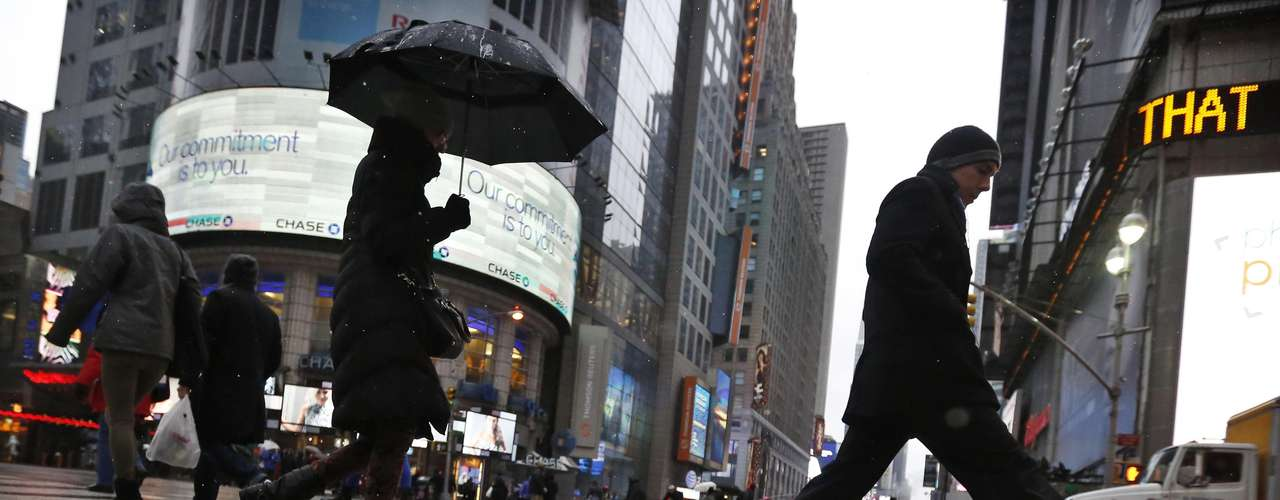 People walk through the sleet and rain in New York's Times Square, February 8, 2013. The Northeast U.S. is bracing for a large winter storm that has caused flight cancellations. REUTERS/Brendan McDermid (UNITED STATES - Tags: ENVIRONMENT)