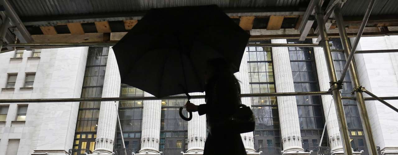 A woman walks past the New York Stock Exchange in New York's financial district, February 8, 2013. The Northeast U.S. is bracing for a large winter storm that has caused flight cancellations. REUTERS/Brendan McDermid (UNITED STATES - Tags: ENVIRONMENT)
