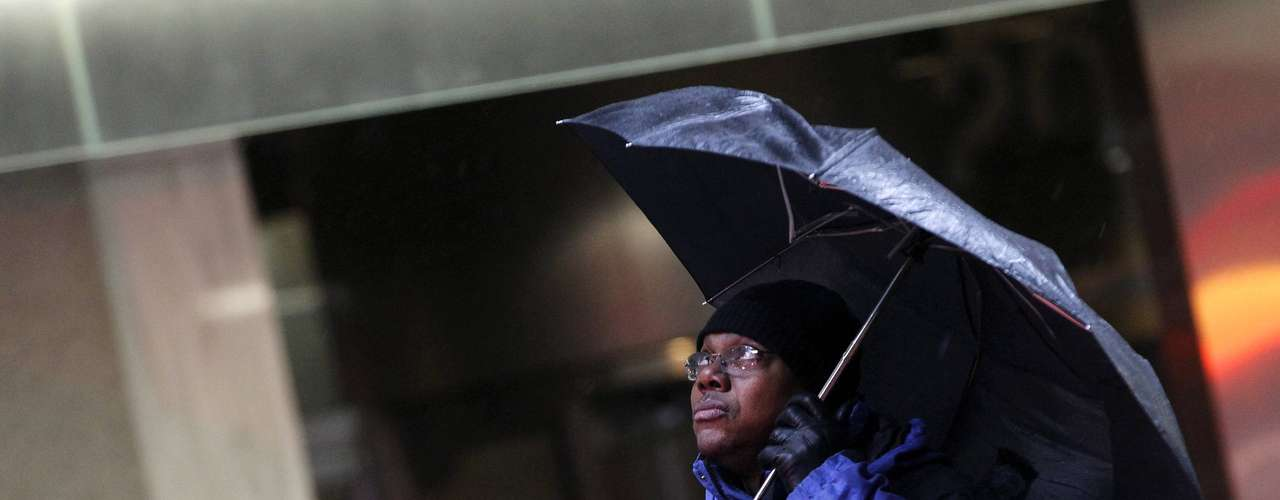 A building security guard looks up from his umbrella in New York's financial district, February 8, 2013. The Northeast U.S. is bracing for a large winter storm that has caused flight cancellations. REUTERS/Brendan McDermid (UNITED STATES - Tags: ENVIRONMENT)