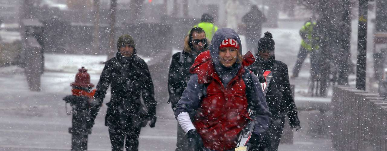 A woman carries her skis as the snow begins to fall in Boston, Massachusetts February 8, 2013 at the beginning of what is forecasted to be a major winter snow storm.   REUTERS/Brian Snyder    (UNITED STATES - Tags: ENVIRONMENT)