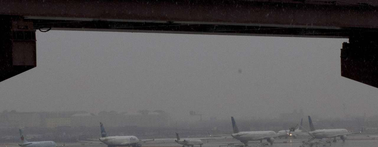 Airplanes wait in line on the runway during the arrival of a winter storm at the Newark Liberty International airport in New Jersey February 8, 2013. A blizzard blew into the northeastern United States on Friday, cutting short the workweek for millions who feared being stranded as state officials ordered roads closed ahead of what forecasters said could be record-setting snowfall. Officials across the region closed schools and more than 3,000 flights were canceled.  REUTERS/Eduardo Munoz (UNITED STATES - Tags: ENVIRONMENT DISASTER TRANSPORT)