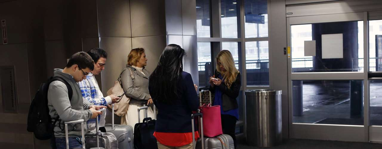 Family members wait for their ride at Boston Logan International Airport, to go back home after their flight to Brazil was cancelled due to a massive winter storm, in Boston, Massachusetts, February 8, 2013. Blizzard warnings were in effect from New Jersey through southern Maine, with Boston expected to bear the brunt of the massive storm that could set records.   REUTERS/Bizuayehu Tesfaye   (UNITED STATES - Tags: ENVIRONMENT)
