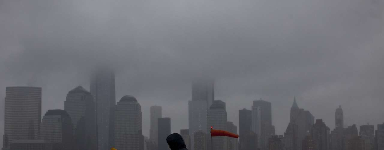 A man walks at the Paulus Hook pier during the arrival of a winter storm from the skyline of New York's Lower Manhattan, in Exchange Place, New Jersey, February 8, 2013. A blizzard blew into the northeastern United States on Friday, cutting short the workweek for millions who feared being stranded as state officials ordered roads closed ahead of what forecasters said could be record-setting snowfall. Officials across the region closed schools and more than 3,000 flights were canceled.  REUTERS/Eduardo Munoz (UNITED STATES - Tags: ENVIRONMENT DISASTER CITYSCAPE TPX IMAGES OF THE DAY)