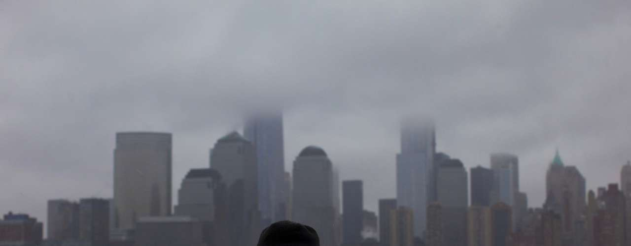 A man takes cover from a winter storm from the skyline of New York's Lower Manhattan, in Exchange Place, New Jersey, February 8, 2013. A blizzard blew into the northeastern United States on Friday, cutting short the workweek for millions who feared being stranded as state officials ordered roads closed ahead of what forecasters said could be record-setting snowfall. Officials across the region closed schools and more than 3,000 flights were canceled. REUTERS/Eduardo Munoz (UNITED STATES - Tags: ENVIRONMENT DISASTER CITYSCAPE TPX IMAGES OF THE DAY)