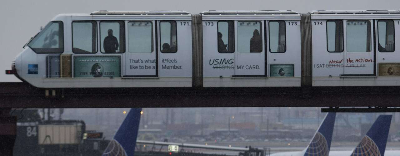 Passengers ride an AirTrain travelling near airplanes during the arrival of a winter storm at the Newark Liberty International airport in New Jersey February 8, 2013. February 8, 2013. A blizzard blew into the northeastern United States on Friday, cutting short the workweek for millions who feared being stranded as state officials ordered roads closed ahead of what forecasters said could be record-setting snowfall. Officials across the region closed schools and more than 3,000 flights were canceled. REUTERS/Eduardo Munoz (UNITED STATES - Tags: ENVIRONMENT TRANSPORT DISASTER)