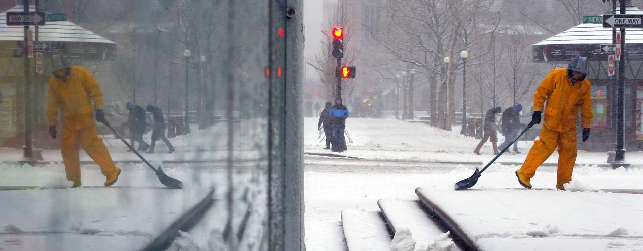 A worker is reflected in the glass wall of a bus stop as he shovels the snow off the steps of the Boston Public Library in Boston, Massachusetts February 8, 2013. A blizzard blew into the northeastern United States on Friday, cutting short the workweek for millions who feared being stranded as state officials ordered roads closed ahead of what forecasters said could be record-setting snowfall.   REUTERS/Brian Snyder    (UNITED STATES - Tags: ENVIRONMENT)