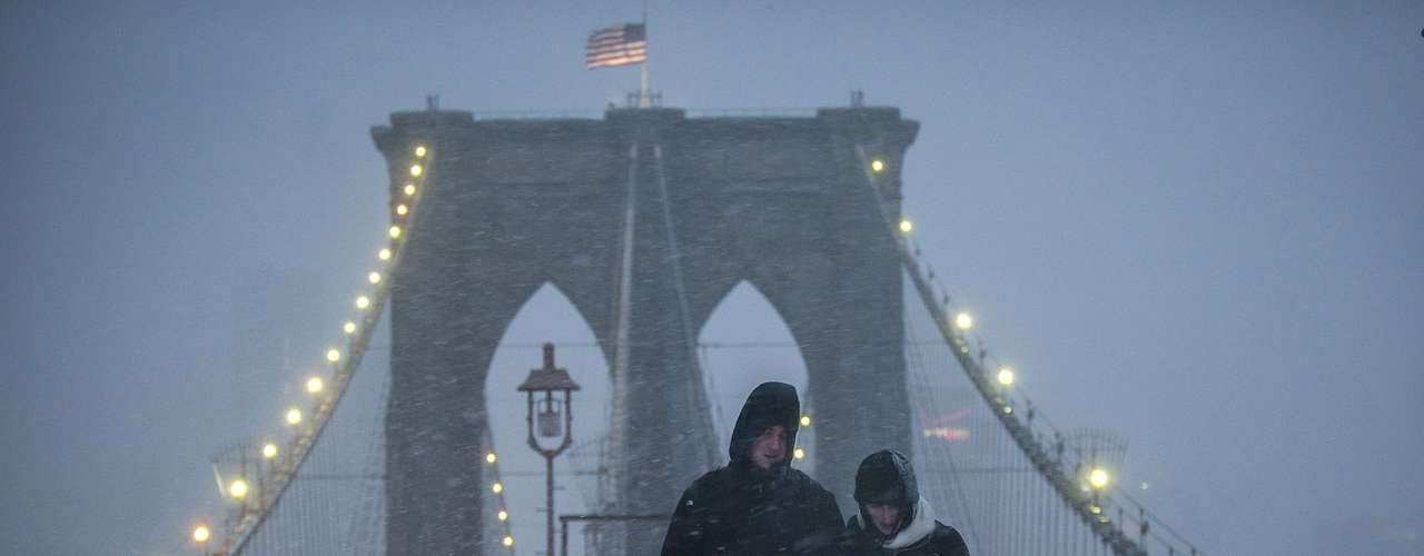 A couple makes their way across the Brooklyn Bridge through snow and wind in New York, February 8, 2013. A blizzard blew into the northeastern United States on Friday, cutting short the workweek for millions who feared being stranded as state officials ordered roads closed ahead of what forecasters said could be record-setting snowfall. From New York to Maine, the storm began gently, dropping a light dusting of snow, but officials urged residents to stay home, rather than risk getting stuck in deep drifts when the storm kicks up later Friday afternoon. REUTERS/Keith Bedford (UNITED STATES - Tags: ENVIRONMENT)