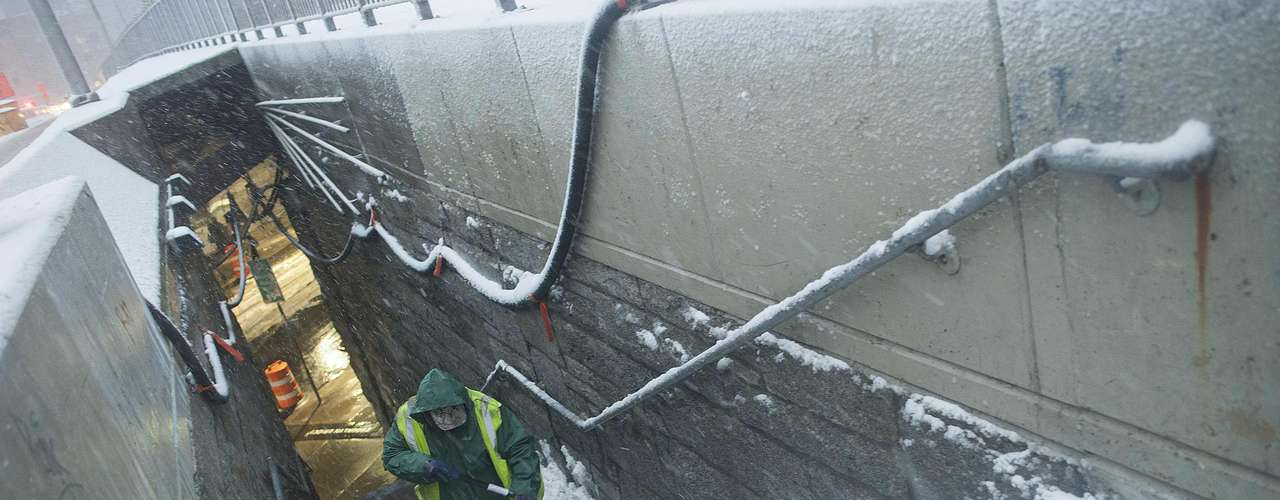 A New York City sanitation worker shovels snow from a stairway in New York, February 8, 2013.  A blizzard blew into the northeastern United States on Friday, cutting short the workweek for millions who feared being stranded as state officials ordered roads closed ahead of what forecasters said could be record-setting snowfall. From New York to Maine, the storm began gently, dropping a light dusting of snow, but officials urged residents to stay home, rather than risk getting stuck in deep drifts when the storm kicks up later Friday afternoon.REUTERS/Keith Bedford (UNITED STATES - Tags: ENVIRONMENT)